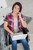 Mujer sonriente que se sienta en la silla de ruedas usando el ordenador que practica surf en Internet Imagenes de archivo