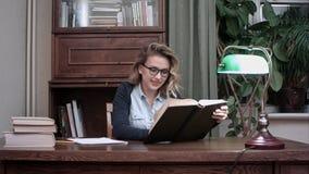 Mujer sonriente que se sienta en su escritorio y que pasa feliz a través de un libro fotos de archivo