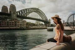 Mujer sonriente que se sienta en Sydney delante del puente del puerto fotografía de archivo libre de regalías