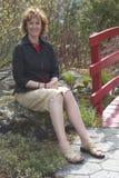 Mujer sonriente que se sienta en una roca en un día asoleado imágenes de archivo libres de regalías