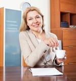 Mujer sonriente que se sienta en una tabla en la oficina Foto de archivo
