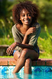 Mujer sonriente que se sienta por la piscina con los pies en agua Imagenes de archivo