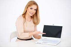 Mujer sonriente que se sienta que muestra el ordenador portátil en la tabla Foto de archivo