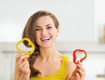 Mujer sonriente que sostiene dos rebanadas de paprika rojo y amarillo Fotos de archivo libres de regalías
