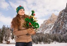 Mujer sonriente que sostiene el árbol de navidad en el frente del montañas Imagenes de archivo