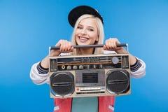 Mujer sonriente que sostiene el equipo estéreo portátil Imagen de archivo libre de regalías