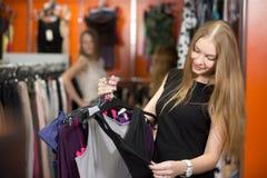 Mujer sonriente que sostiene el manojo de ropa en tienda Fotografía de archivo