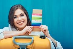 Mujer sonriente que sostiene el pasaporte con el boleto Fotos de archivo
