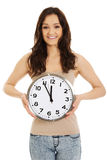 Mujer sonriente que sostiene el reloj grande Imagen de archivo