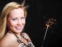 Mujer sonriente que sostiene el sparkler del Año Nuevo Fotos de archivo