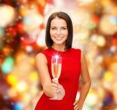 Mujer sonriente que sostiene el vidrio de vino espumoso Fotos de archivo