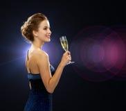 Mujer sonriente que sostiene el vidrio de vino espumoso Fotos de archivo libres de regalías