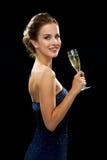Mujer sonriente que sostiene el vidrio de vino espumoso Imágenes de archivo libres de regalías