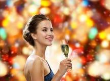 Mujer sonriente que sostiene el vidrio de vino espumoso Foto de archivo