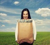 Mujer sonriente que sostiene la bolsa de papel con el dinero Fotos de archivo libres de regalías