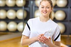 Mujer sonriente que sostiene la botella de agua en el gimnasio de la aptitud Imagenes de archivo