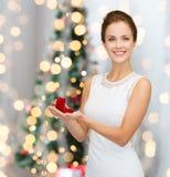 Mujer sonriente que sostiene la caja de regalo roja con el anillo Fotografía de archivo libre de regalías