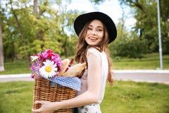 Mujer sonriente que sostiene la cesta con las flores, las bebidas y la comida Imagen de archivo