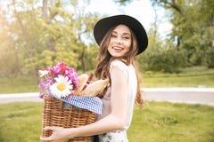 Mujer sonriente que sostiene la cesta con las flores, las bebidas y la comida Imagen de archivo libre de regalías