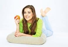 Mujer sonriente que sostiene la manzana roja que miente en un piso Foto de archivo libre de regalías