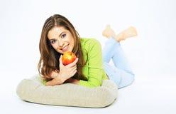 Mujer sonriente que sostiene la manzana roja que miente en un piso Fotos de archivo libres de regalías