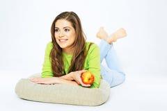 Mujer sonriente que sostiene la manzana roja que miente en un piso con l cruzado Fotos de archivo libres de regalías