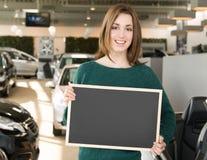 Mujer sonriente que sostiene la pizarra dentro de la concesión de coche Fotos de archivo