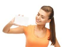 Mujer sonriente que sostiene la tarjeta en blanco blanca Fotos de archivo