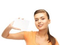 Mujer sonriente que sostiene la tarjeta en blanco blanca Fotografía de archivo libre de regalías