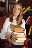 Mujer sonriente que sostiene los libros en la biblioteca imagen de archivo libre de regalías