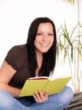 Mujer sonriente que sostiene un libro Imagen de archivo libre de regalías