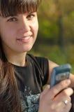 Mujer sonriente que sostiene un móvil Imagen de archivo libre de regalías