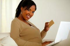 Mujer sonriente que sostiene un oro de la tarjeta de crédito imagenes de archivo