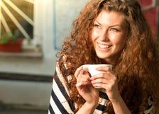 Mujer sonriente que sostiene una bebida caliente Foto de archivo