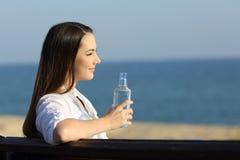 Mujer sonriente que sostiene una botella de agua en la playa Imagen de archivo