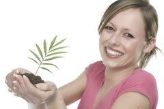 Mujer sonriente que sostiene una planta Imagen de archivo libre de regalías