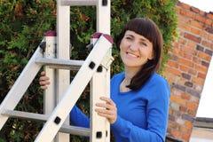 Mujer sonriente que sube en la escalera de aluminio en jardín Foto de archivo