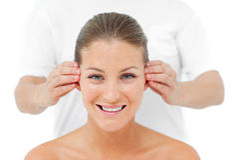 Mujer sonriente que tiene un masaje principal en un balneario Imagen de archivo libre de regalías