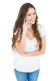 Mujer sonriente que tiene una llamada de teléfono Foto de archivo libre de regalías