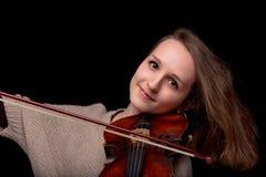 Mujer sonriente que toca el violín en fondo negro Fotos de archivo