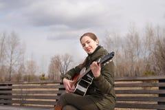 Mujer sonriente que toca la guitarra Imagen de archivo libre de regalías