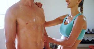 Mujer sonriente que toca a un hombre muscular en el gimnasio 4k almacen de video