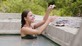 Mujer sonriente que toma el baño en piscina termal y la aplicación de la máscara del fango en piel de la cara Mujer hermosa en pi almacen de video