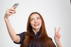 Mujer sonriente que toma el selfie con el teléfono móvil que muestra la muestra de la victoria Imagen de archivo libre de regalías