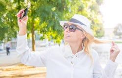 Mujer sonriente que toma el selfie en un día soleado Imágenes de archivo libres de regalías