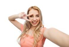 Mujer sonriente que toma el selfie y mostrar el signo de la paz Foto de archivo