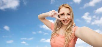 Mujer sonriente que toma el selfie y mostrar el signo de la paz Fotos de archivo libres de regalías