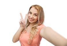 Mujer sonriente que toma el selfie y mostrar el signo de la paz Fotografía de archivo