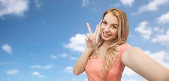 Mujer sonriente que toma el selfie y mostrar el signo de la paz Imagen de archivo