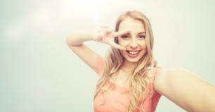 Mujer sonriente que toma el selfie y mostrar el signo de la paz Fotos de archivo